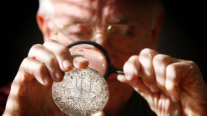 Dr. Chapman (background) views the reverse of the Charlotte Madal with a magnifying class